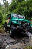 SUV在热带密林- 2013 3月7日,冒险趟过一条岩石河的汽车热心者使用修改过的四轮汽车 免版税库存照片