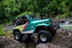 SUV在热带密林- 2013 3月7日,冒险趟过一条岩石河的汽车热心者使用修改过的四轮汽车 库存图片