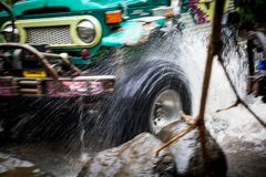 SUV在热带密林- 2013 3月7日,冒险趟过一条岩石河的汽车热心者使用修改过的四轮 免版税图库摄影