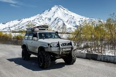 SUV日产徒步旅行队在路乘坐反对火山背景  免版税图库摄影