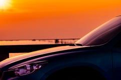 SUV汽车侧视图在混凝土路有体育和现代设计的停放的由海在日落 r 免版税库存图片