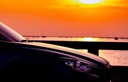 SUV汽车侧视图在混凝土路有体育和现代设计的停放的由海海滩在日落 杂种和电车 库存图片