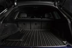 SUV汽车大黑空的后车箱有橡胶席子的和有在汽车特写镜头地板开放载物架的皮革文件夹的  免版税图库摄影