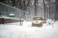 SUV汽车被停止在自动词条门在大雪期间 车通入门户系统 飞雪的季节在winer的在城市 免版税库存图片