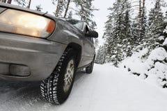 Suv, αυτοκίνητο, που οδηγεί στους χιονώδεις επικίνδυνους όρους Στοκ Φωτογραφία