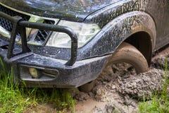 SUV που αποκτάται κολλημένο στη λάσπη, κινηματογράφηση σε πρώτο πλάνο ροδών Στοκ Φωτογραφία