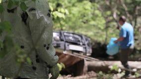 SUV που αποκτάται κολλημένο στο δάσος και τους λαούς που χρησιμοποιούν το βαρούλκο για την υπερνικημένη σύνθετη έκταση απόθεμα βίντεο