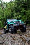 SUV в тропических джунглях - энтузиаст автомобиля приключения 7-ое марта 2013 wading скалистое река используя доработанный каретн Стоковое Изображение