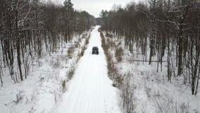 SUV 6x6的鸟瞰图,乘坐在一条积雪的路在冬天森林里,正面图 影视素材
