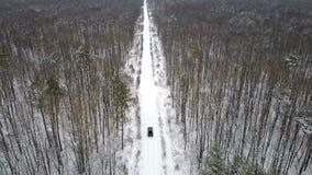 SUV 6x6的鸟瞰图,驾驶在一条积雪的路在冬天森林里,后面看法 影视素材