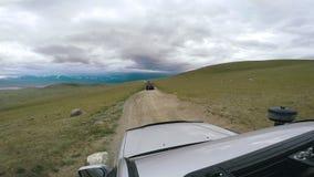SUV berijdt een vallei met bergen op de horizon Autoreis: POV - Standpuntauto die zich langs de weg bewegen aan stock video