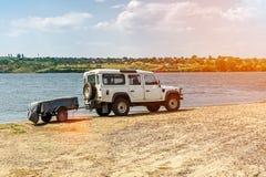 SUV bianco con un rimorchio sulle banche del fiume glare fotografia stock
