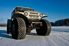 SUV on big wheels. SUV on big wheel on snow Royalty Free Stock Images