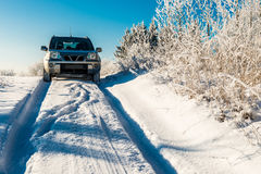 Suv car going through winter snowy road Stock Photo