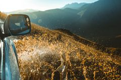 Suv car rides through muddy puddle, off-road track road, with a big splash, during in the background of a mountain landscape. Road Trip Concept stock photography