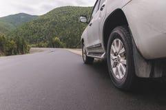 SUV cinzento na estrada asfaltada imagens de stock