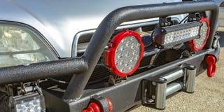 SUV com projetores e o gancho do reboque na grade guardam fotos de stock