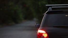SUV con las luces del peligro cerca del camino almacen de metraje de vídeo