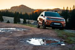 SUV on a country road in mountains at sunrise. Apuseni, Romania - OCT 15, 2017: orange Suzuki Vitara SUV on a country road in mountains at sunrise. beautiful royalty free stock photos