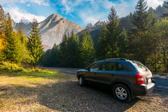 SUV on countryside road in High Tatra mountains. Lovely transportation scenery at sunrise in autumn. disover Slovakia travel by car concept. composite image stock photos