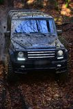 SUV covered with mud on path covered with leaves. Dirty offroad car with fall forest on background. Black crossover with lights turned on, driving with cloud royalty free stock photography