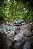 SUV dans la jungle tropicale - risquez 7 mars 2013 l'enthousiaste de voiture pataugeant une rivière rocheuse utilisant la voiture Photos stock