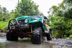 SUV dans la jungle tropicale - risquez 7 mars 2013 l'enthousiaste de voiture pataugeant une rivière rocheuse utilisant la voiture Images libres de droits