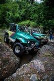 SUV dans la jungle tropicale - risquez 7 mars 2013 l'enthousiaste de voiture pataugeant une rivière rocheuse utilisant la voiture Photos libres de droits
