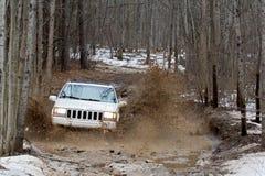 SUV, das tiefen Schlamm durchläuft Stockbilder