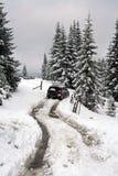 SUV, das Winterstraße weitergeht Lizenzfreie Stockbilder