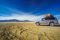 SUV in de Altiplano-woestijn door Uyuni - Bolovia Stock Afbeelding