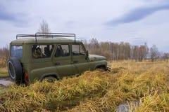 SUV in den Sümpfen Die SUV-Antriebe durch die Sümpfe oder Sümpfe unter Verwendung einer Handkurbel Passierbarer Transport stockbilder