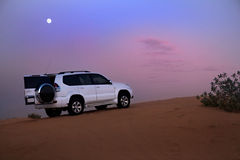 SUV in the desert. Dusk Royalty Free Stock Photography