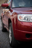 SUV detail. Image showing a close-up of a red SUV, focusing on the headlight and on the reflections of the sorroudnings stock photos
