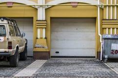 Suv dichtbij garage wordt geparkeerd die stock foto
