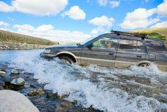 SUV die door de bergrivier wordt bewogen royalty-vrije stock afbeeldingen