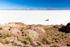 SUV die zout de eilandenlandschap berijden van woestijnsalar de uyuni Stock Fotografie