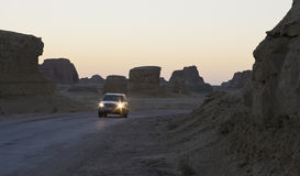 Suv drives in valley at twilight Stock Image