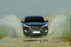 Suv drives through water. Suv drives through flooded road Royalty Free Stock Photography