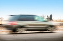 SUV driving fast on a morning commute stock image