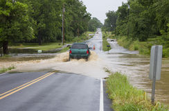 An SUV Driving on Flooded Road. A Dodge SUV makes it safely through a flooded roadway Royalty Free Stock Image