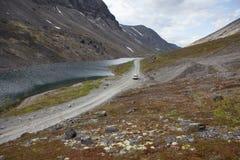 SUV driving on mountain road near lake, Khibiny in Kola Peninsula, Russia Royalty Free Stock Image