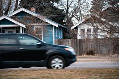 SUV driving through a small town stock photography