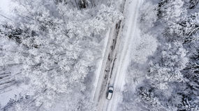 Suv driving in white snowy evergreen forest on slipery asphalt road. Aerial view from drone Royalty Free Stock Photo