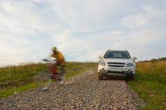 SUV e motociclista em declive Imagens de Stock