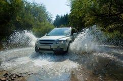 SUV in een bergstroom Stock Afbeeldingen