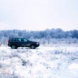 SUV en campo del invierno Imagen de archivo libre de regalías