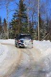 SUV en el camino snowny en bosque fotografía de archivo libre de regalías