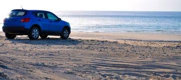 SUV en la playa (a) Foto de archivo libre de regalías