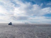 SUV en la sal de Uyuni plana Fotos de archivo